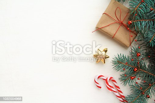 istock Christmas background. Composition with Christmas gift box, fir tree branch, candy canes and decorations on white background. Top view with copy space. 1032004968