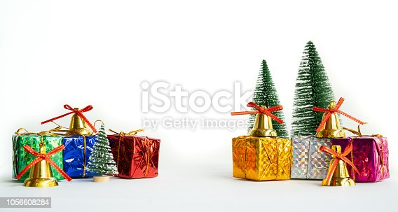 865140324 istock photo Christmas background concept. Christmas gift box and tree with golden bells, pine cones, on white background 1056608284
