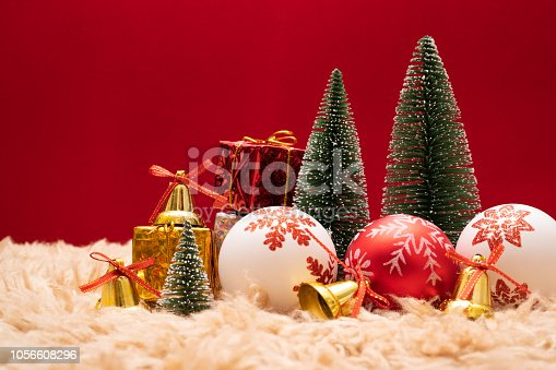 865140324istockphoto Christmas background concept. Christmas gift box and tree with golden bells, pine cones, red and white ball on red background 1056608296