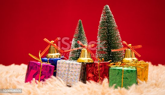 865140324istockphoto Christmas background concept. Christmas gift box and tree with golden bells, pine cones, red and white ball on red background 1056608320
