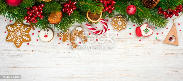 istock Christmas background concept, decorated holiday tree branches and gingerbread cookies 1044690066