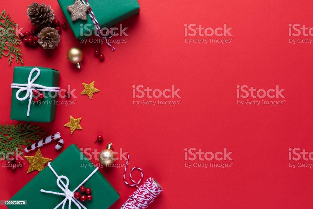 Weihnachten Hintergrund Konzept. Draufsicht der grüne Geschenk Box rot Weihnachtssocke mit Fichte Zweige, Tannenzapfen, roten Beeren und Bell auf rotem Grund. – Foto