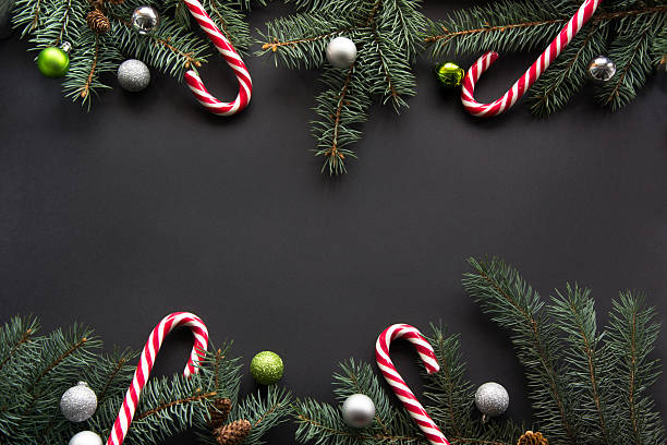 christmas background. fir-tree branches on black with copyspace. top view. - vintage ornaments stock photos and pictures