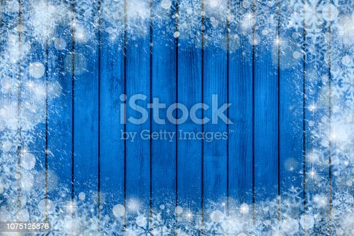1076063742 istock photo Christmas background frame with snow and snowflake. new year decorations on blue wooden background 1075125876