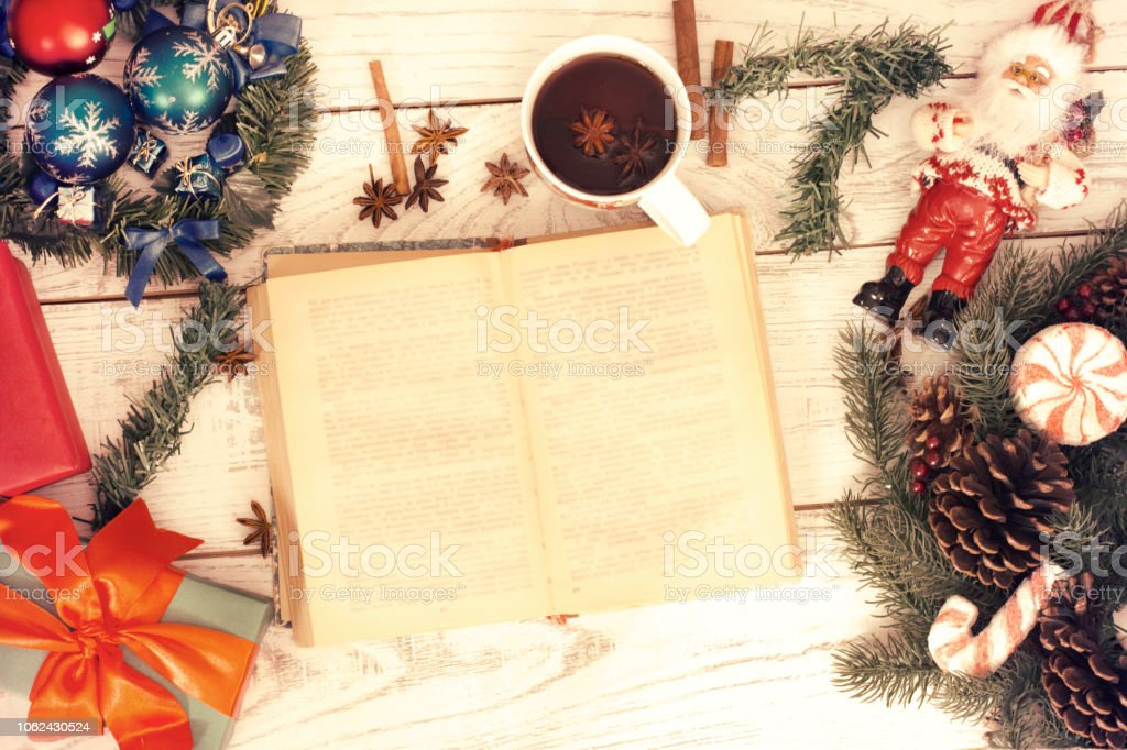 Christmas background. Girl reading book and drinking tea near gift...
