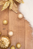 Christmas background. Gold Christmas balls on a wooden background. Winter holidays concept. Top view with copy space, vertical image.