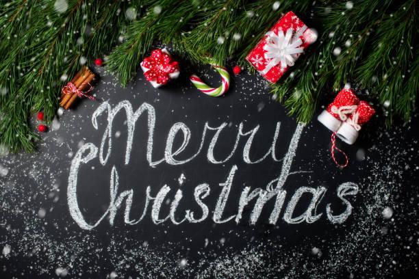 weihnachten hintergrund. frohe weihnachten-schriftzug. tafel, tanne, geschenk und andere decoratios - texte zu weihnachten stock-fotos und bilder