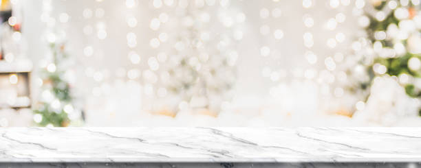 christmas background of marble table top with abstract warm living room decor with christmas tree string light blur bokeh with snow,holiday backdrop, panoramic mock up banner for display of product. - christmas table foto e immagini stock