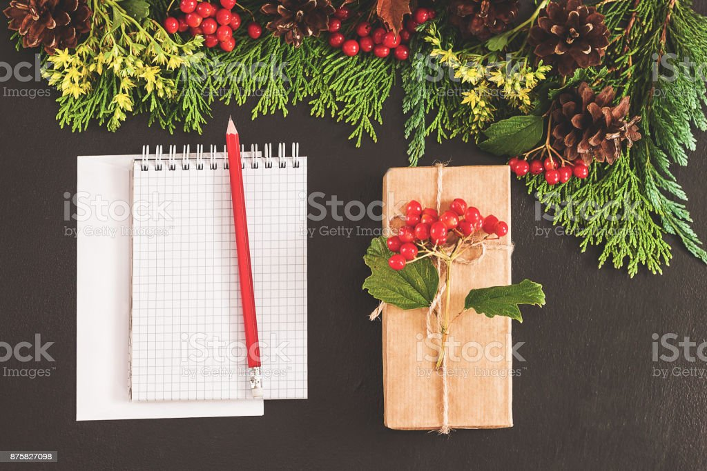 Christmas background or Xmas card. Preparation for winter holiday. A notebook on the black table, flat lay style. Planning concept. Top view. Festive mood stock photo
