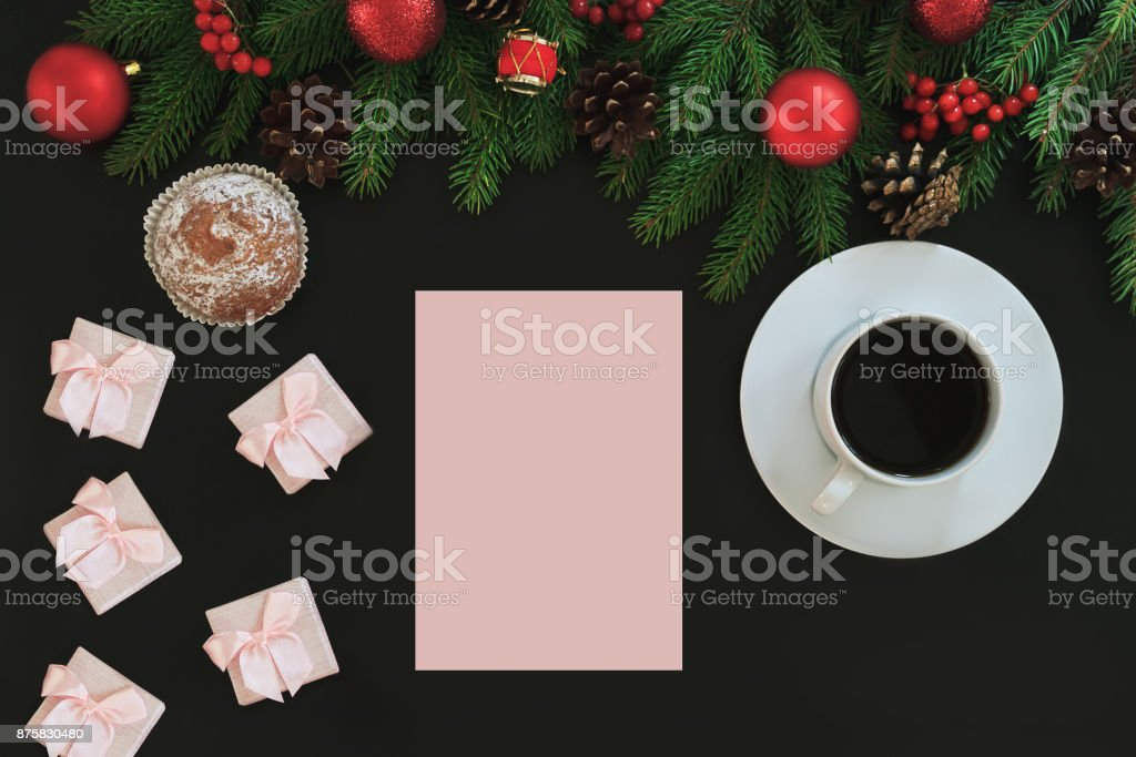 Christmas background or Xmas card  with decorations fir, gift box and red ornamen. List with space for Holiday Greetings.  Top view. Goal, planning winter holiday. Black backtop stock photo