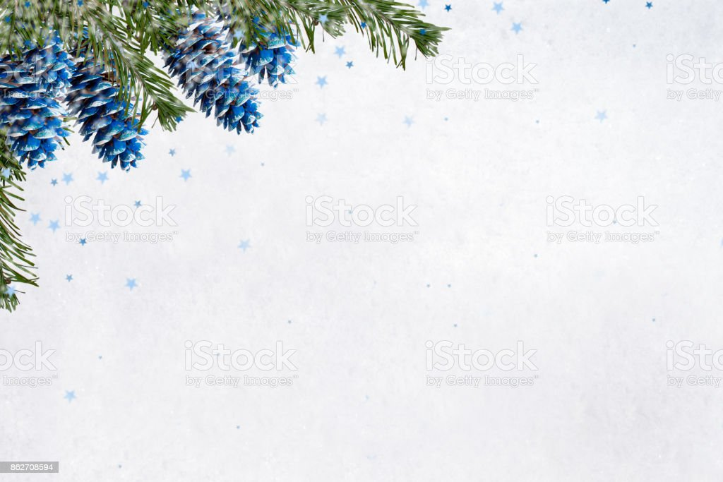 Christmas background. Painted blue fir cones and green branches  on background of white snow with small blue asterisks. - foto stock