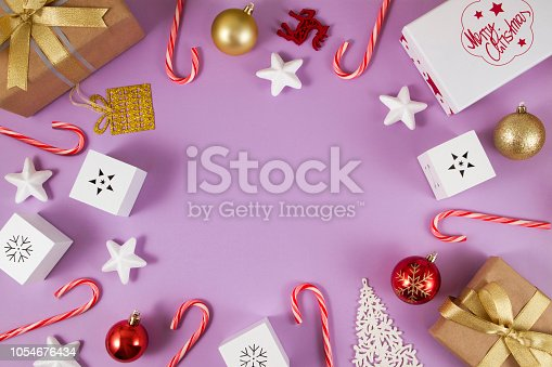 Christmas ornaments, gifts and candy canes on soft purple background