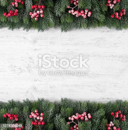 Christmas background with fir tree branches on white wooden background.