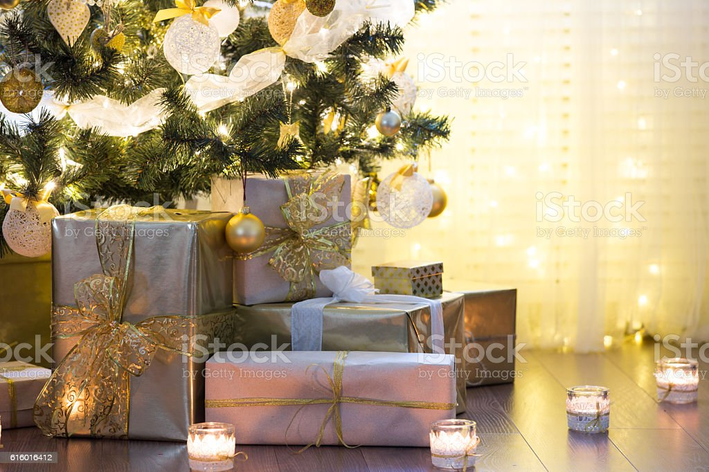 Christmas background Tall christmas tree, beautifully decorated with balls, bows and lights. Lots of christmas gifts under the tree. Candles on wooden floor. Apartment Stock Photo