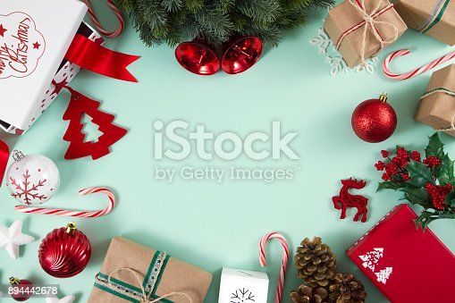 Christmas ornaments, gifts and candy canes on mint green background.