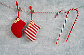 Christmas background. Red Christmas socks and candy canes on gray background. Copy space