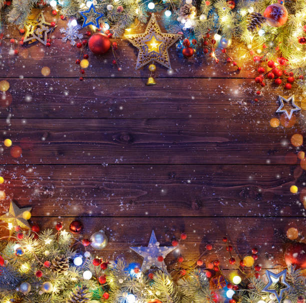 christmas background - snowy fir branches and lights on dark table - christmas stock photos and pictures