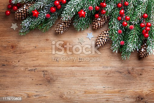 Christmas background. Snowy fir tree branches with fir cones and red berries on wooden board. Top view with space for text and design.