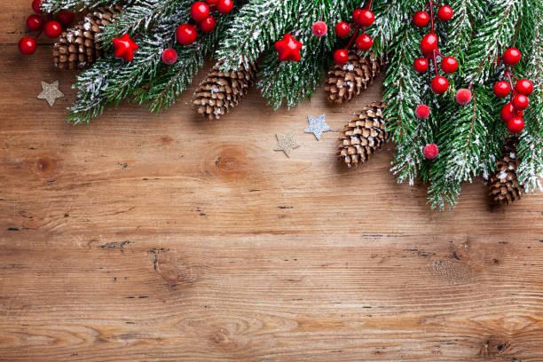 sfondo natalizio. rami di abete innevati con coni di abete e bacche rosse su tavola di legno. visualizzazione superiore con spazio per il testo. - albero sempreverde foto e immagini stock