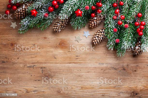 Photo of Christmas background. Snowy fir tree branches with fir cones and red berries on wooden board. Top view with space for text.