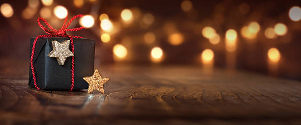Christmas background with a gift Festive shining Christmas background with a gift and bokeh religious celebration stock pictures, royalty-free photos & images