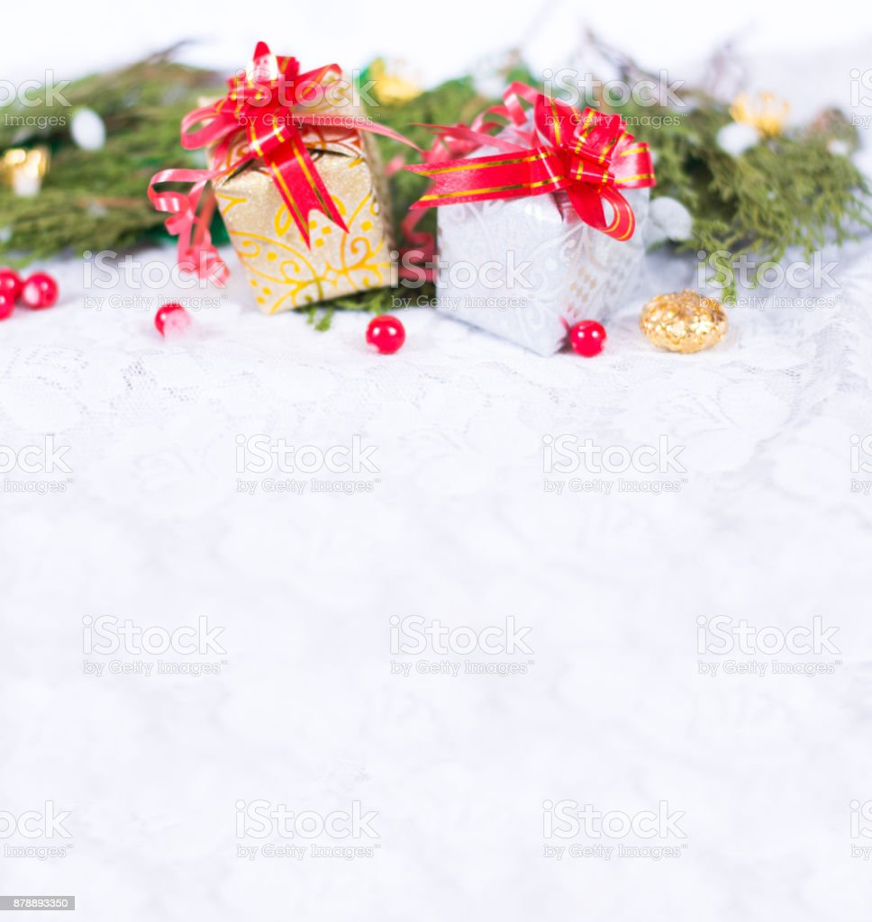 Christmas background with a red ornament, golden gift box, berries and fir in snow stock photo