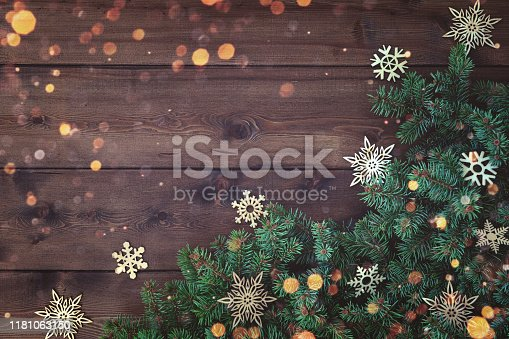 Rustic Natural Christmas background with border of fluffy green fir branches and wooden snowflakes on textured dark brown plank wood background. Copy space for text, flat lay, top view. Corner frame.
