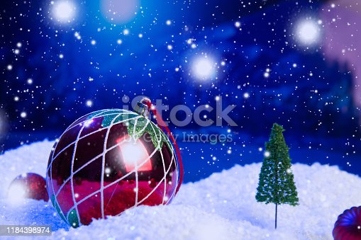 istock Christmas background with Christmas balls on snow over fir-tree, night sky and moon. Shallow depth of field. Christmas background. Fairy tale. Macro. Artificial magic dreamy world. 1184398974