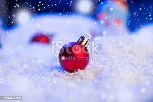 istock Christmas background with Christmas balls on snow over fir-tree, night sky and moon. Shallow depth of field. Christmas background. Fairy tale. Macro. Artificial magic dreamy world. 1189376198
