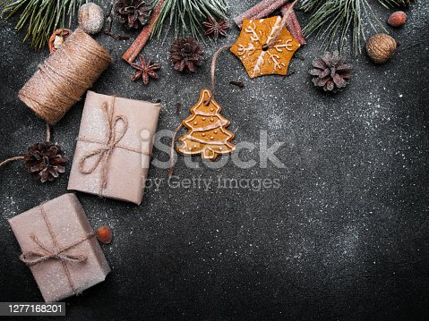 Christmas background with decorations. Christmas presents, gingerbreads, pine twigs and cones covered with snow on dark background