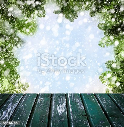 istock Christmas Background with Empty Wooden Deck Table with Winter Snow, Bokeh and Xmas Tree Twig 887437582