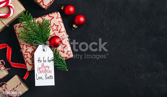 istock Christmas background with fir branches and a gift box with a red bow on a dark concrete background. 1186085744