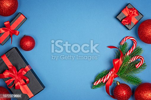 1076063742 istock photo Christmas background with fir tree branches and gift box on blue background. Holiday new year Top view with copy space for your design 1072379664