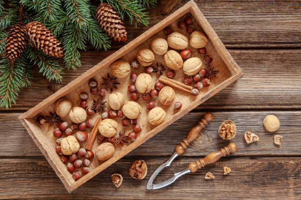 Fundo de Natal com galhos de árvore do abeto, cones, castanhas e especiarias em caixa de madeira e quebra-nozes. Vista superior, close-up na mesa de madeira vintage - foto de acervo