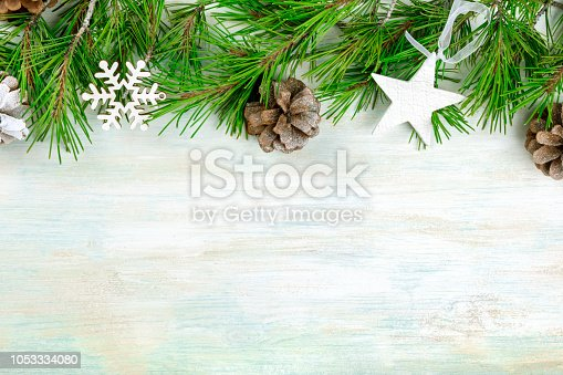 istock Christmas background with fir tree branches, cones, snow, xmas decorations and copy space 1053334080