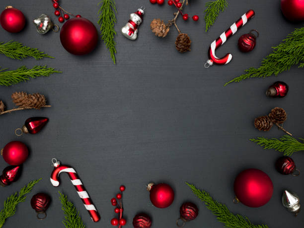 christmas background with frame with red baubles, green branches and other christmas items on blackboard stock photo