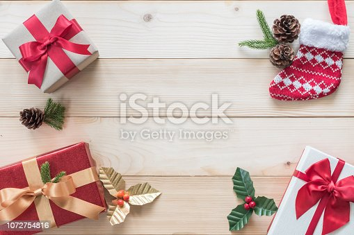 istock Christmas background with gift box, red satin ribbon and spruce twig decoration on white pine wood table for boxing day, winter seasonal holiday and new year celebration 1072754816