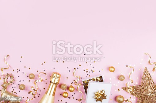 istock Christmas background with golden gift or present box, champagne and holiday decorations on pink pastel table top view. 1063366708