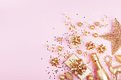 istock Christmas background with golden gift or present box, champagne and holiday decorations on pink pastel table top view. Greeting card. Flat lay. 1071116060