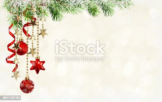 istock Christmas background with green pine twigs, hanging red decorations and silk twisted ribbons 884109190