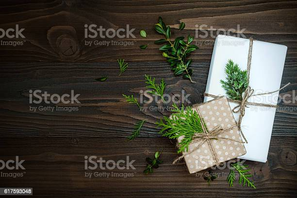Photo of Christmas background with hand crafted presents  on rustic wooden table