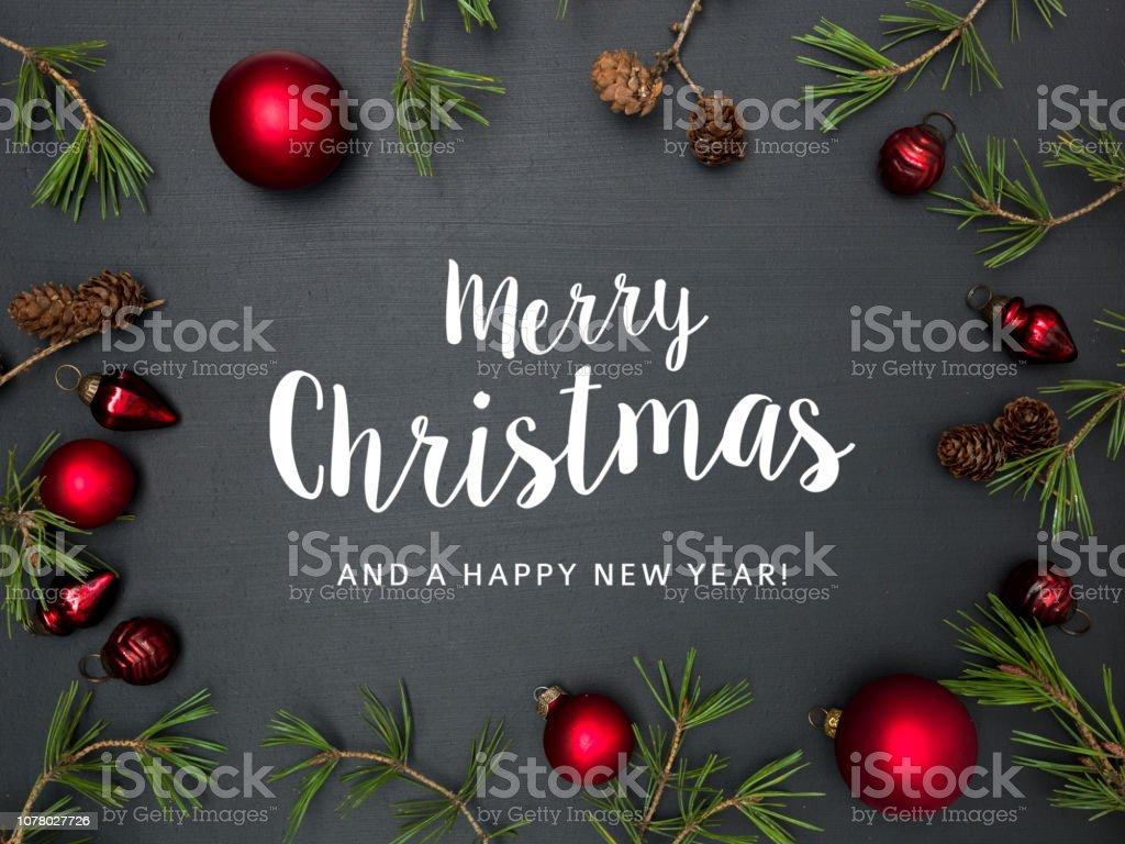 Weihnachten Hintergrund mit Schriftzug Frohe Weihnachten, mit Rahmen mit roten Kugeln, grüne Zweige und andere Weihnachtsartikel an Tafel – Foto