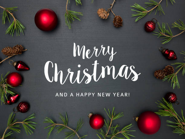 christmas background with lettering merry christmas, with frame with red baubles, green branches and other christmas items on blackboard stock photo