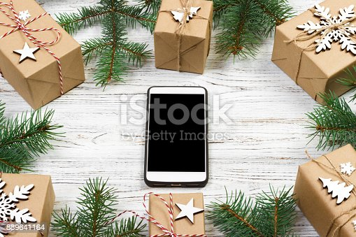 istock Christmas background with mobile phone with blank screen, gifts, fir branches on wooden background, copy space. Flat lay, top view. Christmas application, mock up 889641164