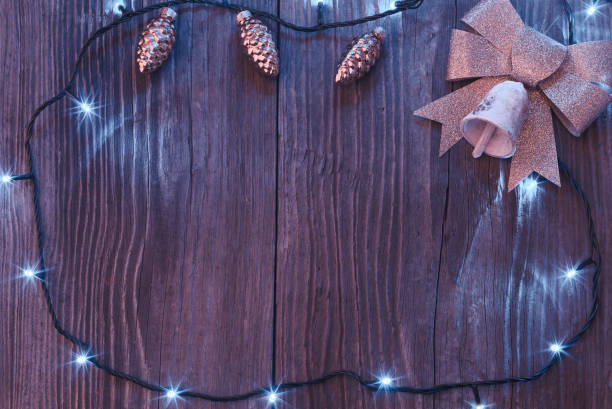 Christmas background with pine cone baubles, golden bow and ringing bell stock photo