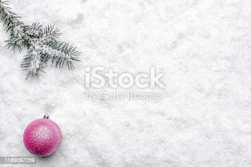 Christmas background with snow, christmas ornament and fir branch, top view