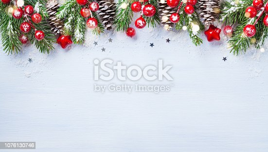 istock Christmas background with snowy fir branches, cones and bokeh lights. Holiday banner or card. 1076130746