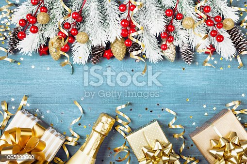 1076063742 istock photo Christmas background with snowy fir tree, gift box, champagne and holiday decorations on blue wooden table top view. Greeting card concept. 1065833660