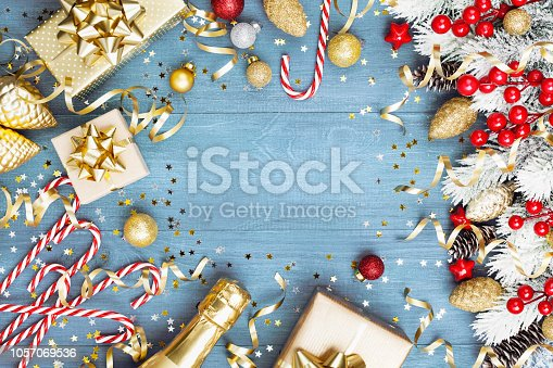 1076063742 istock photo Christmas background with snowy fir tree, gift or present box, champagne and holiday decorations on blue wooden table top view. 1057069536