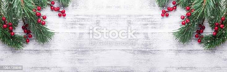 istock Christmas background with tree branches and holly berries. White wooden table. Snowfall drawing effect 1064735646